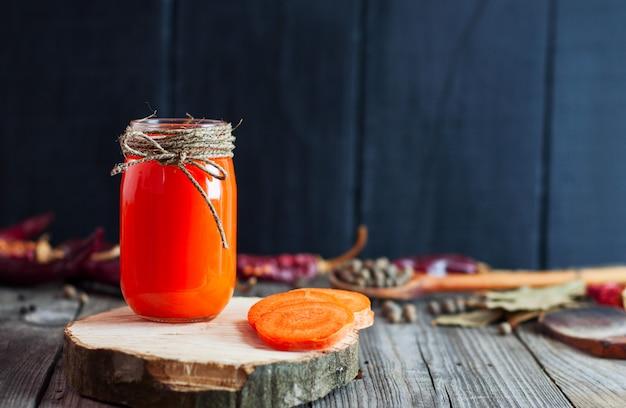 Jarra de suco de cenoura fresca numa superfície de madeira