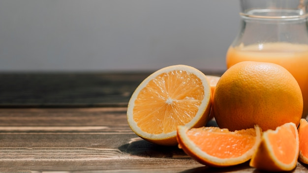 Jarra de suco de laranja delicioso cercado por laranjas com espaço de cópia