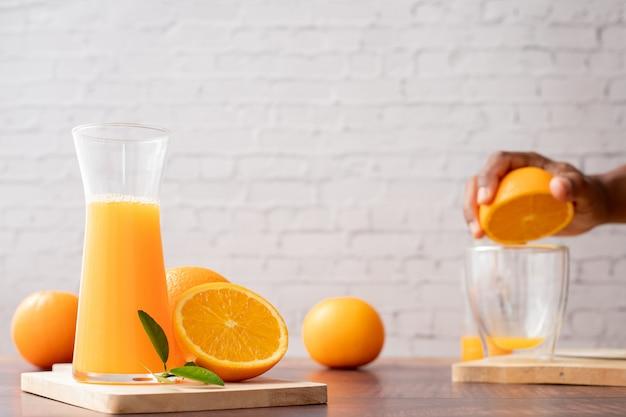 Jarra de suco de laranja espremido na hora com mão humana espremendo a laranja, sem adição de açúcar.