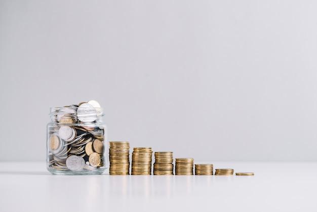 Jarra de vidro cheia de dinheiro na frente de moedas empilhadas decrescentes