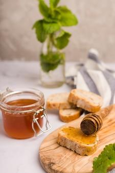 Jarra de vidro cheia de mel com colher de mel