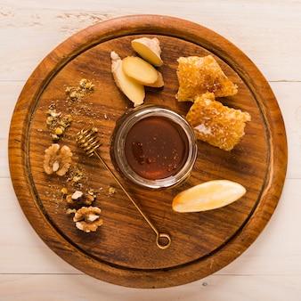 Jarra de vidro cheia de mel na bandeja de madeira
