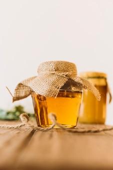 Jarra de vidro cheia de mel na mesa de madeira
