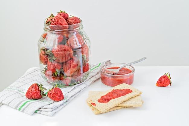 Jarra de vidro cheia de morangos maduros e pronto para comer geléia de morango