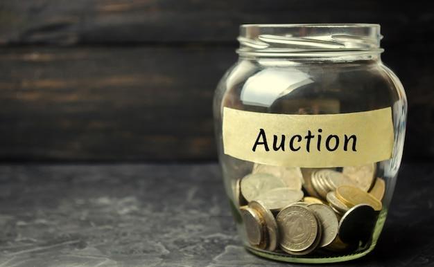 Jarra de vidro com dinheiro e a inscrição auction