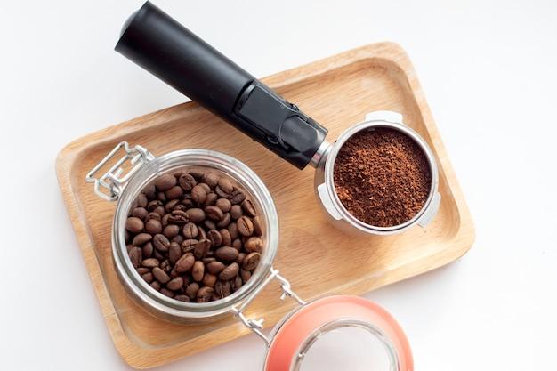 Jarra de vidro com grãos de café e porta-café de filtro com café moído na bandeja de madeira.