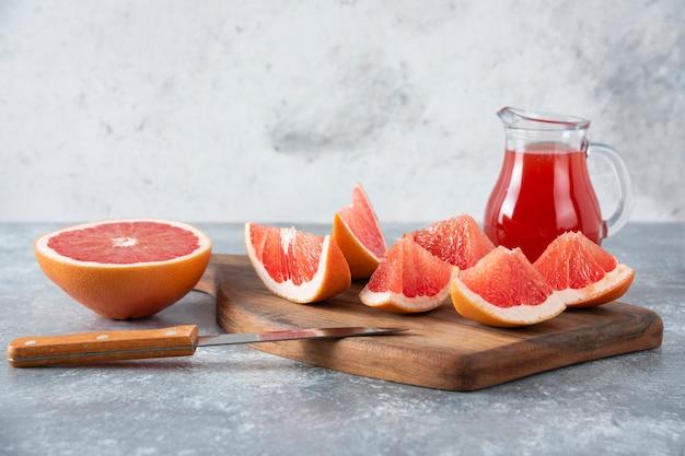 Jarra de vidro com suco de toranja fresco com fatias de frutas.