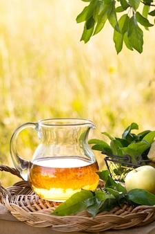 Jarra de vidro com vinagre de cidra ou suco e maçãs maduras frescas.