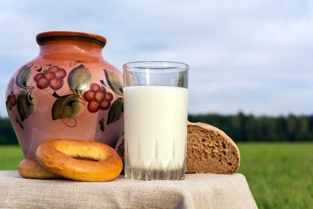 Jarra de vidro de cerâmica com rosquinhas de leite e pão rústico ao ar livre em um fundo de prado