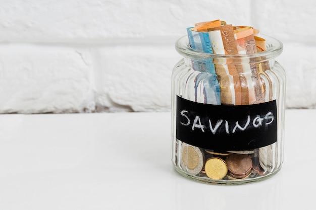 Jarra de vidro de poupança com notas e moedas de euro na