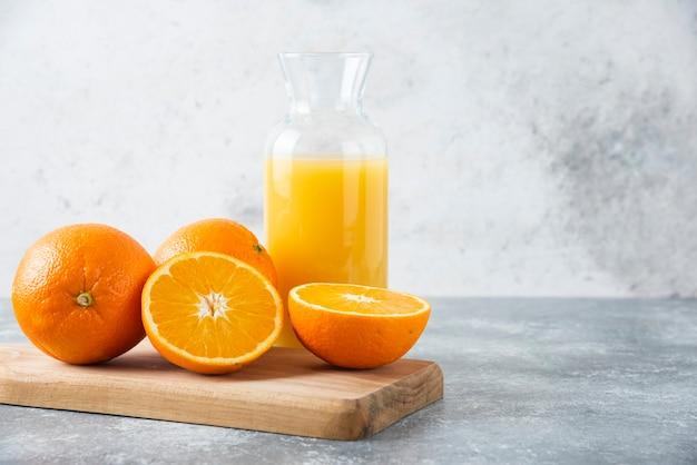 Jarra de vidro de suco com frutas fatiadas de laranja em uma placa de madeira.