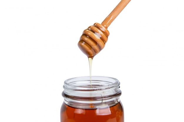 Jarra de vidro mel e dipper alta acima isolado no branco