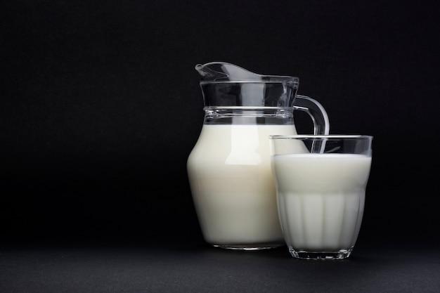 Jarra e copo de leite isolado no preto com espaço de cópia de texto, conceito de produtos lácteos