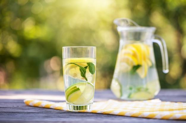 Jarra e copo de limonada caseira na mesa de madeira