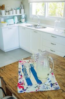 Jarra e copos com suco de limonada na cozinha
