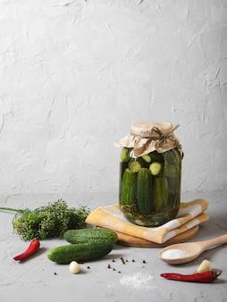 Jarra grande com pepinos fermentados, sal em uma colher de pau e temperos em um concreto.
