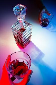 Jarra quadrada de vidro com licor e dois copos de vidro. duas pessoas bebem álcool vista de cima