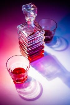 Jarra quadrada de vidro com licor e dois copos de vidro. vista de cima