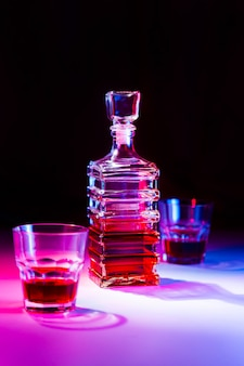 Jarra quadrada de vidro com licor e dois copos de vidro