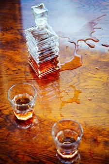 Jarra quadrada velha de uísque com dois copos em uma vista de mesa envernizada