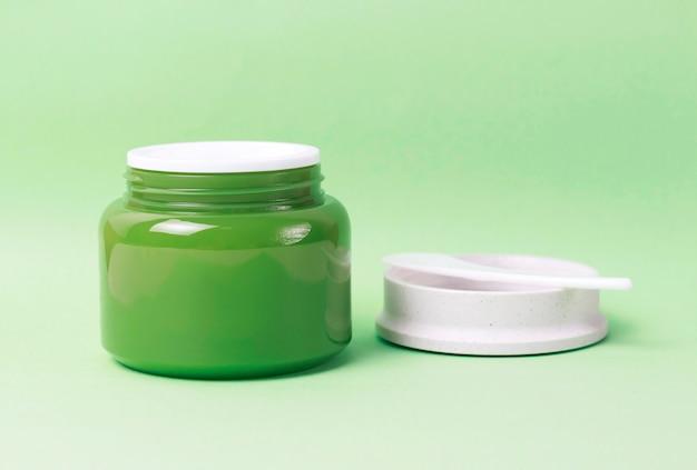 Jarra verde com creme branco e espátula de plástico no fundo, vista lateral, copie o espaço
