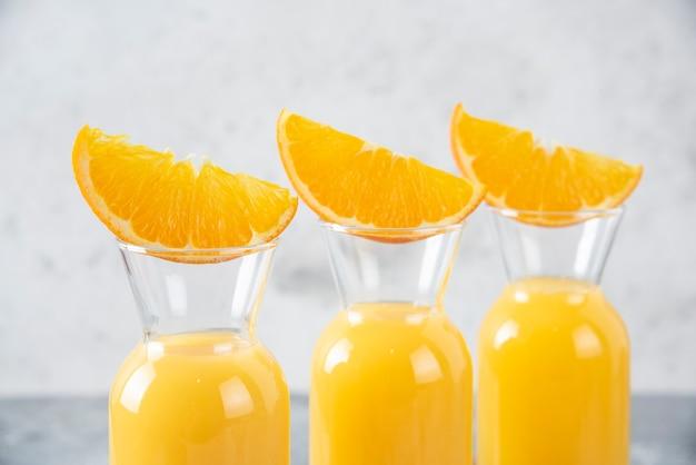 Jarras de vidro de suco com fatias de frutas laranja colocadas sobre uma tábua de madeira.