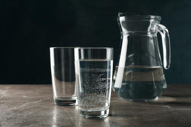 Jarro com água e copos na mesa cinza, espaço para texto