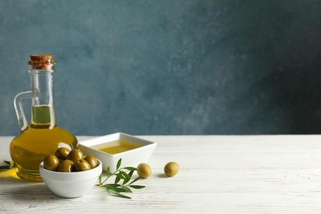 Jarro com azeite e tigela com azeitonas na mesa de madeira, espaço para texto