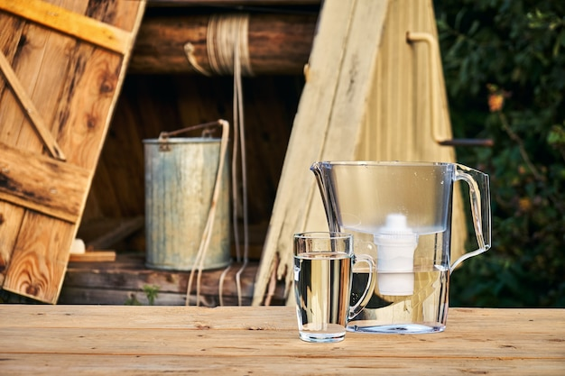 Jarro com filtro de água e um copo de vidro transparente com água limpa em frente a um poço de madeira ao ar livre na noite de verão