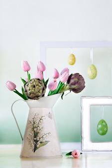 Jarro com tulipas e as alcachofras cor-de-rosa com quadros e os ovos da páscoa brancos no fundo. natureza morta com humor de primavera em tons pastel.