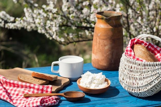 Jarro de barro, cesta, um copo de leite, queijo cottage e pão em uma mesa de placas azuis no fundo de um arbusto florido