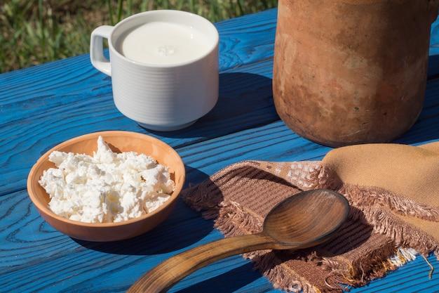Jarro de barro, cesta, uma xícara de leite e queijo cottage em uma mesa de tábuas azuis