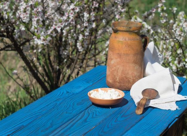 Jarro de barro e queijo cottage em uma mesa de placas azuis contra o fundo de um arbusto florido