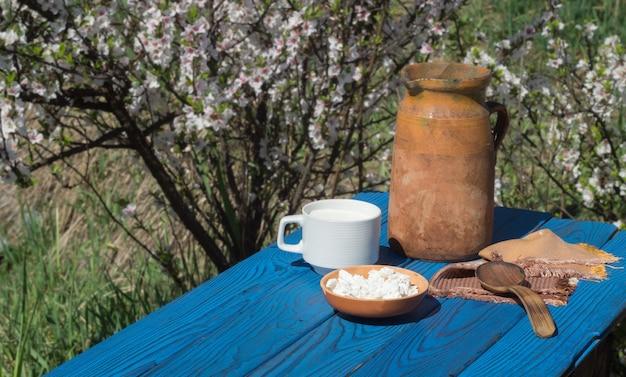 Jarro de barro, um copo de leite e queijo cottage em uma mesa de placas azuis no fundo de um arbusto florido