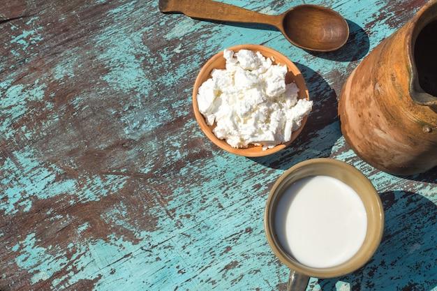 Jarro de barro, um copo de leite e queijo cottage em uma mesa de tábuas azuis claras. vista do topo