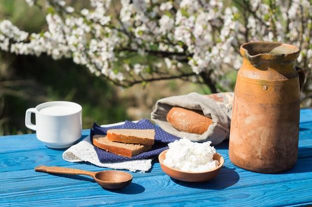 Jarro de barro, um copo de leite, queijo cottage e pão em uma mesa de placas azuis no fundo de um arbusto florido