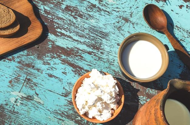 Jarro de barro, um copo de leite, queijo cottage e pão em uma mesa de tábuas azuis claras. vista do topo
