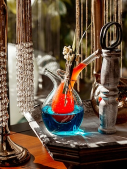 Jarro de bebidas exclusivo com duas partes, preenchido com cocktails de laranja e azuis