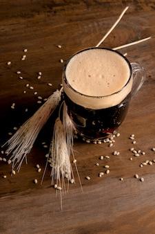 Jarro de cerveja com cevada de espiga na mesa de madeira