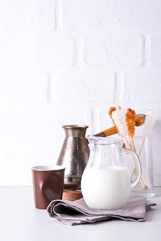 Jarro de leite e café moído para fazer uma bebida em casa, sobre uma bancada de pedra contra uma parede branca da cozinha
