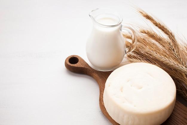 Jarro de leite fresco delicioso na placa de madeira