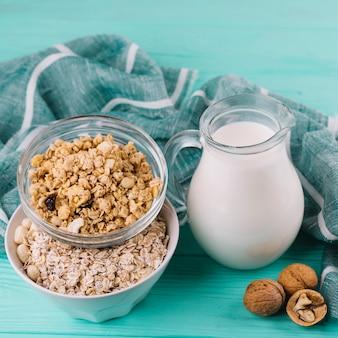 Jarro de leite; tigelas de cereais e nozes na mesa de madeira verde