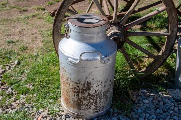 Jarro de leite velho ao lado de uma carroça