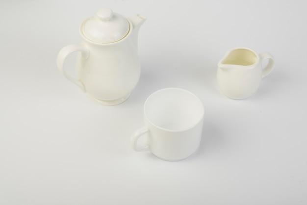 Jarro de leite; xícara e bule de cerâmica no fundo branco