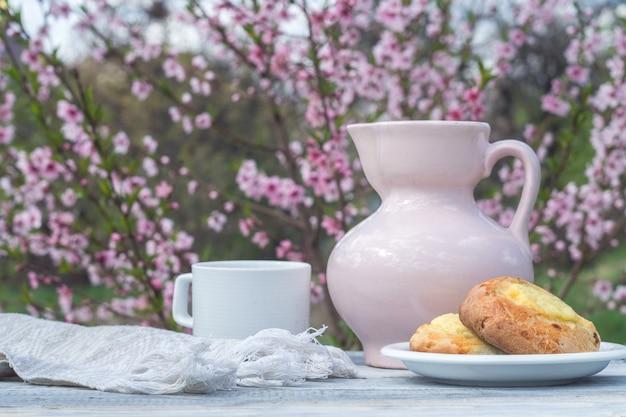 Jarro de porcelana rosa, copo branco e padaria em uma mesa de quadros brancos contra o fundo de um arbusto florido