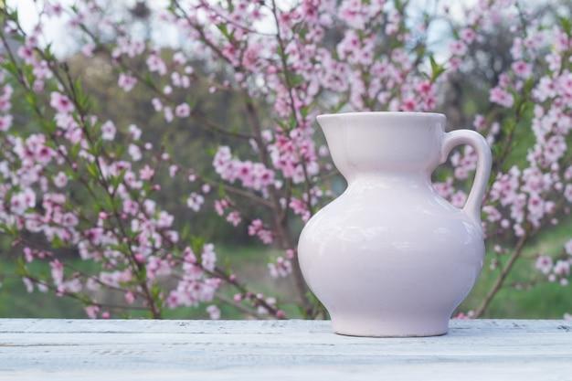 Jarro de porcelana rosa em uma mesa de quadros brancos contra o fundo de um arbusto florido