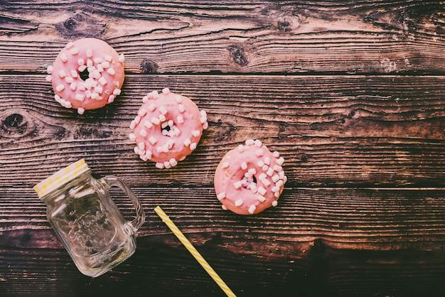 Jarro de suco com palha colorida e anéis de espuma vitrificados cor-de-rosa na placa de madeira.