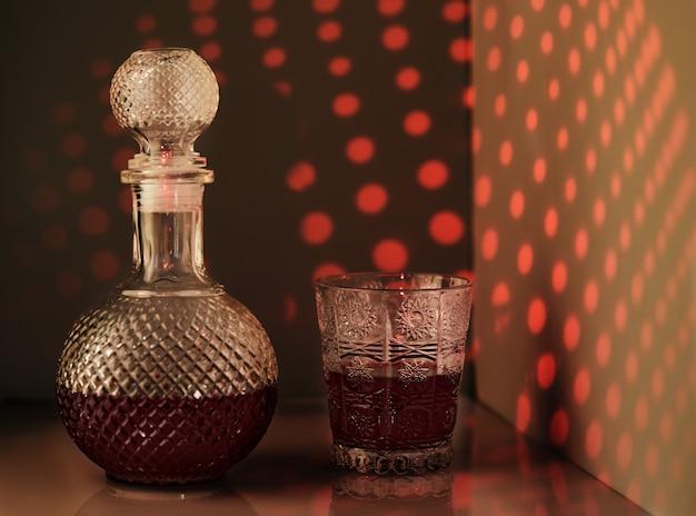Jarro de vinho tinto e taça de vinho, com iluminação inusitada em forma de padrões na parede.