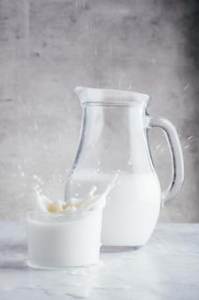 Jarro e copo cheio de leite de vaca fresco