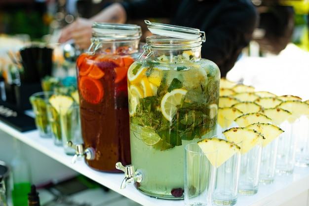 Jarros de limonada com limão laranja e frutas na mesa
